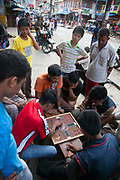 Dhading, the high street. Men playing Ludo, a very popular game in Nepal amongst men.