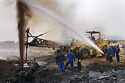 """Firefighters from the KWWK (Kuwait Wild Well Killers) attempt to kill an oil fire in the Rumaila field by guiding a """"stinger"""" that will pump drilling mud into the damaged well. A """"stinger"""" is a tapered pipe on the end of a long steel boom controlled by a bulldozer. Drilling mud, under high pressure, is pumped through the stinger into the well, stopping the flow of oil and gas. A sudden wind shift after a sandstorm caused the oil to blow back on the workers and equipment, causing a very dangerous situation because the oil and gas could have easily ignited. The Rumaila field is one of Iraq's biggest oil fields with five billion barrels in reserve. Many of the wells are 10,000 feet deep and produce huge volumes of oil and gas under tremendous pressure, which makes capping them very difficult and dangerous. This well is of relatively low volume. Rumaila is also spelled Rumeilah.     ."""