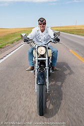 Jay Allen rides his hopped up Harley-Davidson FXR south on highway 79 to Sturgis on the Michael Lichter - Sugar Bear ride during the annual Sturgis Black Hills Motorcycle Rally. SD, USA. August 3, 2014.  Photography ©2014 Michael Lichter.