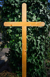 Plain simple wooden cross grave cemetery ivy