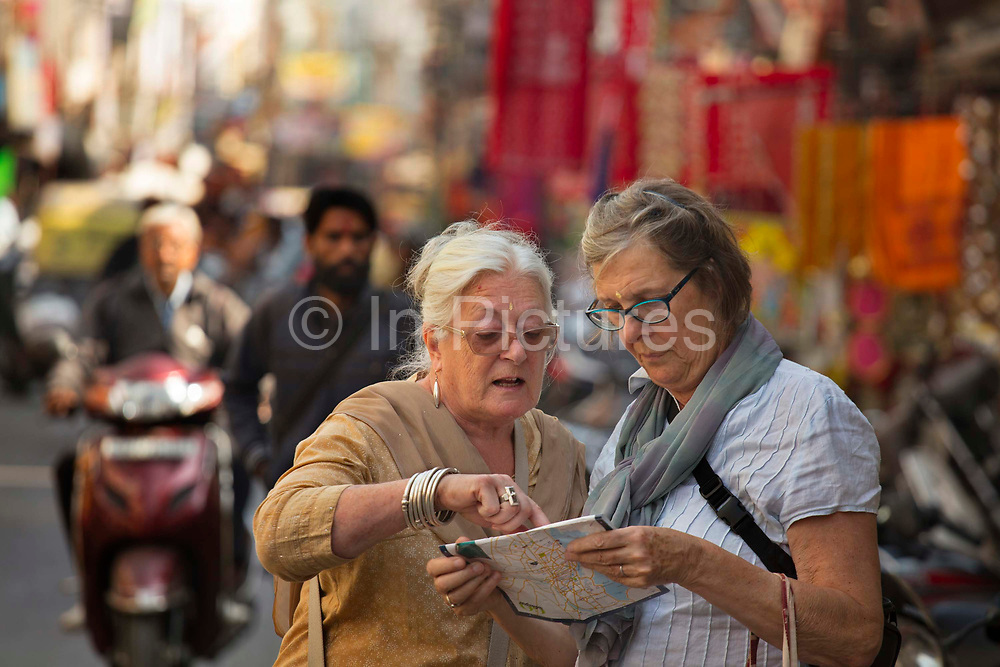 Lost elderly women western tourists studying a map in the busy street on the 20th January 2018  in the city of Udaipur, India. Behind her 2 Rajasthani women with traditional saris and veils share a scooter in the busy traffic.