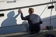 A man cleans the hull of his boat, on 8th January 2019, in Ramsgate, Kent, England. The Port of Ramsgate has been identified as a 'Brexit Port' by the government of Prime Minister Theresa May, currently negotiating the UK's exit from the EU. Britain's Department of Transport has awarded to an unproven shipping company, Seaborne Freight, to provide run roll-on roll-off ferry services to the road haulage industry between Ostend and the Kent port - in the event of more likely No Deal Brexit. In the EU referendum of 2016, people in Kent voted strongly in favour of leaving the European Union with 59% voting to leave and 41% to remain.
