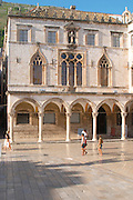 the arched porch and facade of the Sponza palace on the Luza Lodge Loggia Square on the Pred Dvorom street. Three tourist walking past Dubrovnik, old city. Dalmatian Coast, Croatia, Europe.