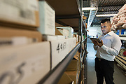 An employee checks inventory in a warehouse on an electronic tablet.