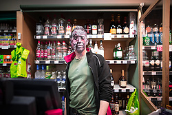 © Licensed to London News Pictures . 30/10/2016 . Manchester , UK . A man working the graveyard shift at Spar on Piccadilly . Revellers on a night out , many in fancy dress , on the weekend before Halloween . Photo credit : Joel Goodman/LNP