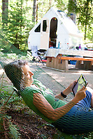 A woman (50-60) relaxes in a hammock while reading an ipad as they camp in BC Parks Miracle Beach campground.