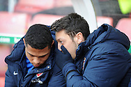Arsenal's Mesut Ozil ® sits in the dugout as a replacement before k/o. Barclays Premier league, Stoke city v Arsenal match at the Britannia Stadium in Staffordshire, England on Saturday 1st March 2014.<br /> pic by Andrew Orchard, Andrew Orchard sports photography.
