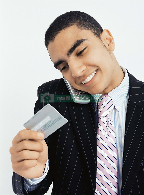 Dec. 05, 2012 - Businessman with mobile and credit card (Credit Image: © Image Source/ZUMAPRESS.com)