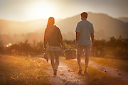 Man and woman walking down a dirt road with a basket of apples.