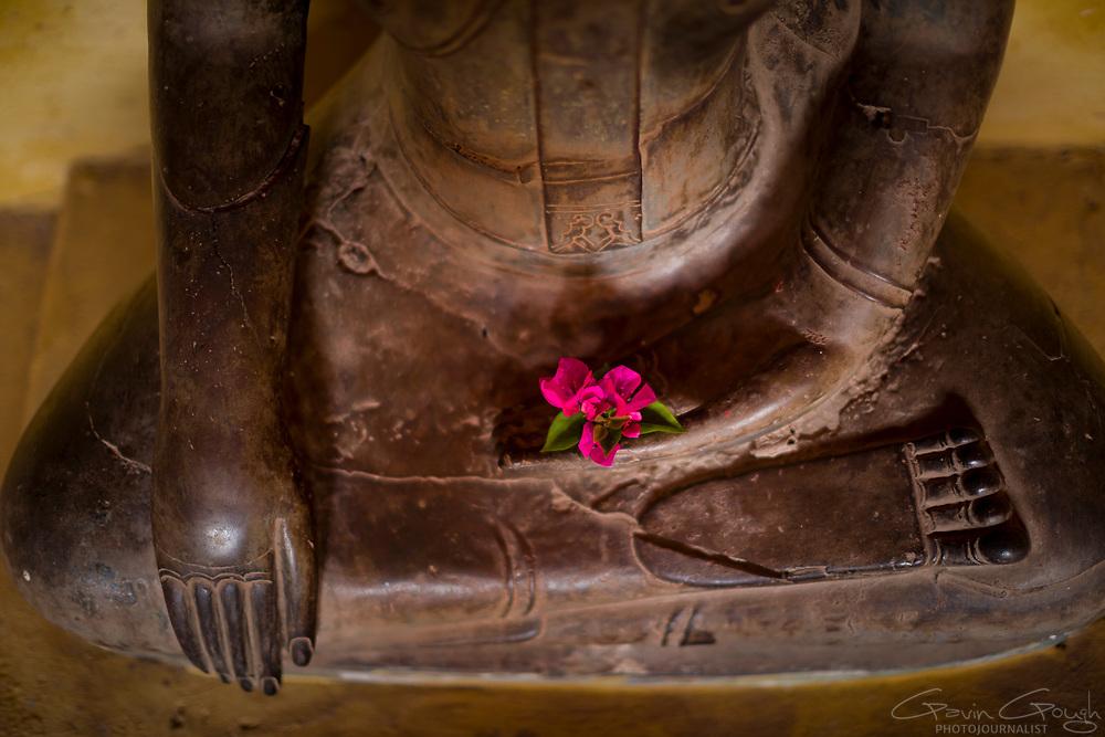 Ancient bronze Buddha statue adopting the Bhumisparsha Mudra or earth-touching hand gesture mudra inside the temple complex, Wat Si Saket, Vientiane, Laos