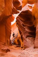 A hiker explores the sandstone slots of the Lower Antelope Canyon, Lake Powell Navajo Tribal Park, Arizona.