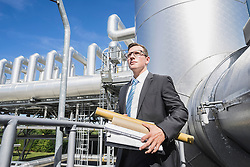 Young businessman standing with documents at geothermal power station, Bavaria, Germany