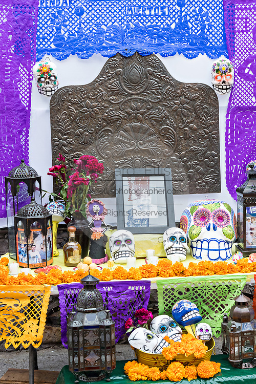 A Dead of the Dead altar known as an ofrenda honoring deceased relatives during the Dia de Muertos festival in San Miguel de Allende, Mexico. The multi-day festival is to remember friends and family members who have died using calaveras, aztec marigolds, alfeniques, papel picado and the favorite foods and beverages of the departed.
