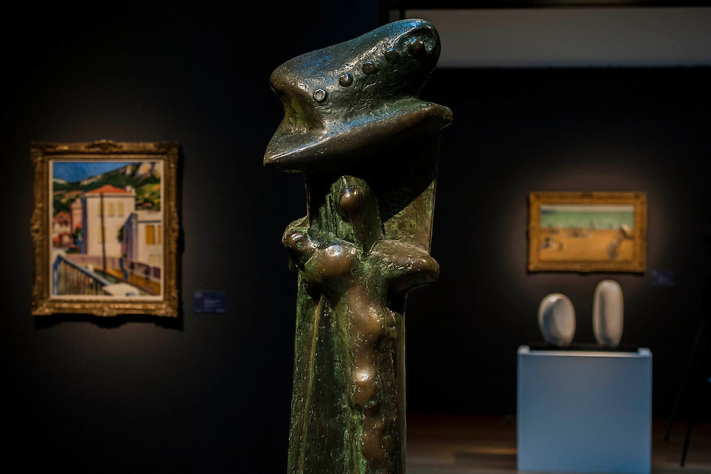 Upright Motive no 8 by Henry Moore with another by Barbara Hepworth in the background - Christie's Modern British and Irish Art Sale which will take place on 19 November 2014. Featuring 35 lots, the auction includes  examples of 20th century British sculpture and painting, such as: John Duncan Fergusson's Poise (estimate: £80,000-120,000); six paintings by L.S. Lowry, led by Coal Barge (estimate: £700,000-1,000,000);  Euan Uglow's masterpiece entitled Three In One (estimate: £500,000-800,000; Figure (Sunion) by Dame Barbara Hepworth (estimate: £600,000-800,000); and sculpture by leading artists of the genre including Henry Moore, Lynn Chadwick, Dame Elisabeth Frink, and Naum Gabo.