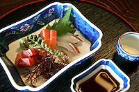 Sashimi or raw fish is a popular appetizer in Japanese cuisine.  the tiny saucers are for dipping into soy sauce and hot mustard or wasabi.