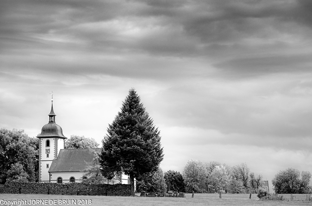 A Church in the Black Forest under a cloudy sky.