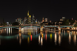 Bridge over river with skyline lit up at night, Frankfurt, Germany