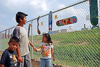 USA, Chicago, August 25, 2009.   Children view environmentally-themed skateboard designs outside the fenced-off Celotex site, possible home for much-needed open space. The Little Village Environmental Justice Organization, headquartered in a predominantly Mexican-American neighborhood of Chicago, campaigns not only against pollution but for clean power, park facilities, urban agriculture, and restoring public transit. LVEJO's staff and volunteers make significant outreach and education efforts, especially for youth. Photo for an HOY feature story by Jay Dunn.