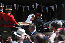 © Licensed to London News Pictures. 19/05/2018. London, UK.  Prince Harry, The Duke of Sussex and Meghan Markle, The Duchess of Sussex are pictured in a horse drawn carriage as they leave St George's Chapel in Windsor Castle following a wedding ceremony. Photo credit: LNP