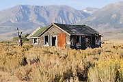 An abandoned home sits in the foreground with the Sierra Mountains in the background in this image of California.