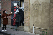A woman wearing a face mask receives her take away coffee through the back door of a coffee shop on 27th November 2020 in Hackney, London United Kingdom. During lockdown 2 in England no costumers were allowed into coffee shops so had to put in an order by the door and then wait for their coffee outside. The coffee shop La Bouche in Broadway Market would take their orders through the front and hand out the drinks out the back.
