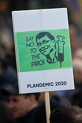"""© Licensed to London News Pictures. 06/12/2020. Manchester, UK. A placard featuring a picture of Bill Gates that reads """" Say no to the prick """" and """" Plandemic 2020 """" . An anti lockdown protest against measures imposed by the British government , designed to limit the spread of Coronavirus , takes place in Piccadilly Gardens in Manchester City Centre . Photo credit: Joel Goodman/LNP"""