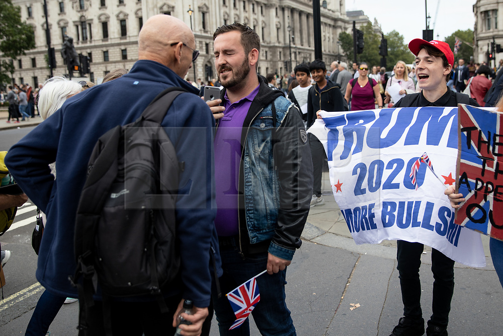 © Licensed to London News Pictures. 05/09/2018. London, UK. NOTE: FILE PHOTO. James Goddard (centre) and Max Hammet-Millay (right) videos a passerby during a Brexit demonstration in September. The pair have been accused of being part of the group calling Conservative MP Anna Soubry a 'Nazi' on Monday this week. [ORIGINAL CAPTION: Anti-Brexit demonstrators and some far-right sympathisers campaign outside the Houses of Parliament, calling for Britain's immediate exit from the EU, and the re-instating of former Foreign Secretary Boris Johnson.] Photo credit : Tom Nicholson/LNP