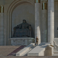 A Mongolian soldier guards the national Parliament Building in Ulaanbaatar, standing between huge bronze scuptures of Genghis Khan and one of his mounted soldiers.