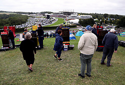 Racegoers get a view of the course from a hill next to the track during Ladies Day of the Qatar Goodwood Festival at Goodwood Racecourse.
