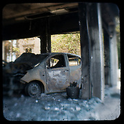 A burned out car dealership n Alexandras avenue, Athens<br /> <br /> Following the murder of a 15 year old boy, Alexandros Grigoropoulos, by a policeman on 6 December 2008 widespread riots, protests and unrest followed lasting for several weeks and spreading beyond the capital and even overseas<br /> <br /> When I walked in the streets of my town the day after the riots I instantly forgot the image I had about Athens, that of a bustling, peaceful, energetic metropolis and in my mind came the old photographs from WWII, the civil war and the students uprising against the dictatorship. <br /> <br /> Thus I decided not to turn my digital camera straight to the destroyed buildings but to photograph through an old camera that worked as a filter, a barrier between me and the city.