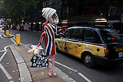 "The character known as Pandemonia, part-parody, living sculpture and fine artist leaves a London fashion show in a London taxi cab during Fashion Week. Writing about herself at www.pandemonia99.com she writes that she is ""a 7ft tall personality often seen at exclusive premiers, events and exhibitions. Post pop, conceptual artist, written about in iD, independent and Vogue publications."" Otherwise, few have any idea about who or what this cartoon character is, or even how this creature secures an invite to parties, society and art events. The writer Poonperm Paitayawat says "".. She is about branding, self-image and lifestyle. She is tapping into the collective unconsciousness. Pandemonia goes beyond pop art."""