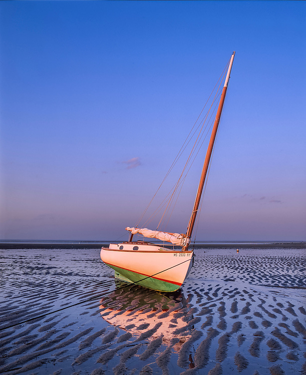 Cat boat on beach at low tide, reflections in water & sand patterns, Brewster, Cape Cod Bay, MA