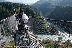 Led Sled's Pat Patterson riding a Royal Enfield Himalayan on the Kushma - Gyadi suspension bridge over the Modi River (the highest, at 384 feet, and longest, at 1,128 feet, suspension bridge in Nepal) during Motorcycle Sherpa's Ride to the Heavens motorcycle adventure in the Himalayas of Nepal. On the sixth day of riding, we went from Tatopani to Pokhara. Saturday, November 9, 2019. Photography ©2019 Michael Lichter.