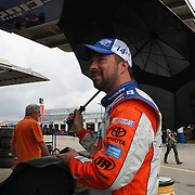 Driver Eric McClure holds an umbrella up by his trailer after the qualifying practice session of the NASCAR Nationwide Drive4COPD 300 was cut short du to bad weather at Daytona International Speedway on Friday, February 21, 2014 in Daytona Beach, Florida.  (AP Photo/Alex Menendez)