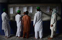 June 14, 2017 - Lahore, Punjab, Pakistan - Pakistani faithful Muslims finds his name in lists of people going to observe Itikaf at Data Darbar Mosque. Itikaf is a spiritual offering in Islam observed in the last ten days of Ramadan during which the believers detach themselves from other people and indulge solely in act of worshiping, keeping the worldly affairs at an arm's length. The observers will spend most of their time in reciting Quran, offering special prayers and seeking blessings from Allah during Itikaf. (Credit Image: © Rana Sajid Hussain/Pacific Press via ZUMA Wire)