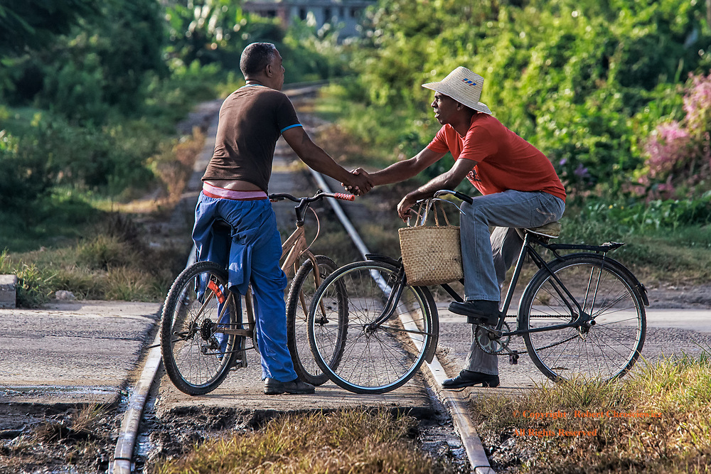 Friendship's Crossroad: Morning and two Cuban men pause to greet the other, while still on bicycles, immediately over a bisecting railway line, Cienfuegos Cuba.