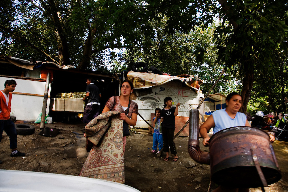 Families rush to remove their possessions from their home as government officials and bulldozers arrive on their street in the Stara Gazela settlements.