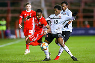 Wales midfielder Rabbi Matondo is tackled by Trinidad and Tobago defender Triston Hodge during the Friendly European Championship warm up match between Wales and Trinidad and Tobago at the Racecourse Ground, Wrexham, United Kingdom on 20 March 2019.