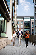 Work colleagues talking and walking poast corporate offices through the business and finance area of St Helier, Jersey, CI