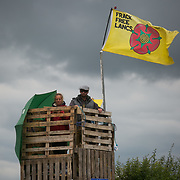 Anti-fracking  activists and protesters outside the gates of Quadrilla's fracking site June 31st, New Preston Road, Lancashire, United Kingdom. Two activists up a tower made of pallets build over night. The struggle against fracking in Lancashire has been going on for years. The fracking company Quadrilla is finally ready to bring in a drill tower to start drilling and anti-frackinhg activists are waiting in front of the gates to block the equipment getting in. Fracking is a destructive and potential dangerous and highly contentious method of extracting gas and this site will be the first of many in the United Kingdom reaching miles out under ground.