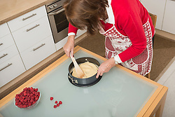Senior woman filling dough into a spring form pan and making smooth, Munich, Bavaria, Germany