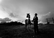 """A gypsy man holding his donkey.<br /> The gipsies call it """"the Cult"""", it is a kind of pact that they get together twice a week in a common hut to pray for good and exorcise the evil. Inside the hut there´s a heavy atmosphere and things seem to be a blend of fantasy and reality. Tens of gipsies form a circle of screams and cries and you can hear a mix of prays, complains, desperation and guilt. A gipsie women faints on the floor almost like she has been exorcised and she had a demon inside her, slowly with the help of the others she recovers.<br /> The truth is that the cult is a way that gipsies chose to express themselves, something that is very much theirs, just like the sound of the gipsies guitars, shows something very real, the suffering of their spirits."""