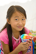 Happy Hmong girl age 11 enjoying her variegated colored snow cone. Hmong Sports Festival McMurray Field St Paul Minnesota USA