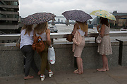Four women huddle underneath umbrellas looking out over the River Thames on a rainy day in London, England, United Kingdom.