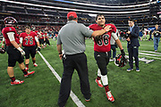 Iraan High School head coach Mark Kirchhoff hugs Steven Garlock after being defeated 49-28 by Bremond High School in the state championship game at AT&T Stadium in Arlington, Texas on December 15, 2016. (Cooper Neill for The New York Times)