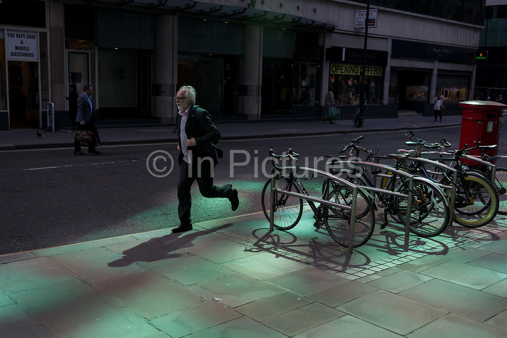 A businessman runs through reflected light from a nearby skyscraper in the City of London, the capitals financial district aka the Square Mile, on 17th May 2018, in London, UK.