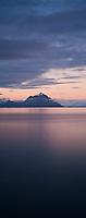 Summer twilight over coastline with distant mountain peak, Stamsund, Lofoten islands, Norway