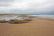 Muddy channel of the River Brue at low tide at its mouth at Burnham on Sea, Somerset, England