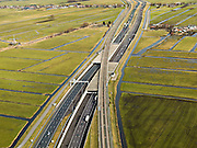 Nederland, Zuid-Holland, Gemeente Alkemade, 20-02-2012; infrastructuur bundel bestaande uit autosnelweg A4 en het hogesnelheidspoor HSL-Zuid. De verdiepte kruising HSL- A4, met viaduct van de hogesnelheidslijn over de lager gelegen snelweg. Veenweidelandschap tussen Roelofarendsveen en Rijpwetering. Onder in beeld .Infrastructure bundle consisting of A4 motorway and the high speed rail HSL. The HST crosses the recessed motorway junction.luchtfoto (toeslag), aerial photo (additional fee required).copyright foto/photo Siebe Swart