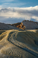 An otherworldly desert landscape in the badlands of Southern Utah as the rolling desert hills lead to the rocky sandstone outcrops at sunset.